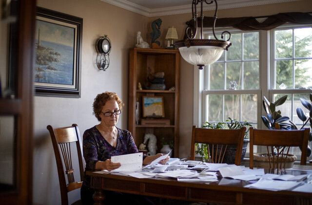 Janet Uhlar sits at her dining room table with letters and photos she received through her correspondence with imprisoned Boston organized crime boss James