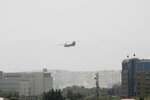 A U.S. Chinook helicopter flies near the U.S. Embassy, left, in Kabul, Afghanistan, Sunday, Aug. 15, 2021. Helicopters are landing at the U.S. Embassy in Kabul as diplomatic vehicles leave the compound amid the Taliban advanced on the Afghan capital. (AP Photo/Rahmat Gul)