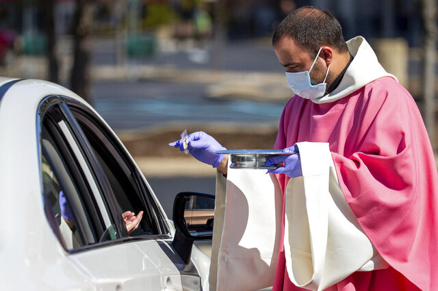 FILE - In this Sunday, March 22, 2020 file photo, the Rev. William A. Mentz, pastor of the Scranton, Pa.-based St. Francis and Clare Progressive Catholic Church, wears a mask and gloves while distributing prepackaged communion to the faithful attending Mass while sitting in their cars in the parking lot of a shopping center in Moosic, Pa. The Progressive Catholic Church is a small denomination operating independently of the Roman Catholic Church. Other Catholic churches in the Scranton area suspended the celebration of mass to help control the spread of COVID-19. (Christopher Dolan/The Times-Tribune via AP)