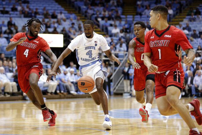 North Carolina's Brandon Robinson (4) chases the ball with Winston-Salem State's Jaylen Alston (4), Justice Kithcart (0) and Robert Colon (1) during the first half of an NCAA exhibition college basketball game in Chapel Hill, N.C., Friday, Nov. 1, 2019. (AP Photo/Gerry Broome)