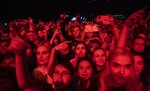 In this photo taken on Monday, Dec. 26, 2018, people cheer during a concert in support of rapper Husky, in Moscow in Moscow, Russia. In recent months, Russian artists have experienced a spike in pressure from the authorities, with a string of concert cancellations and arrests that have brought an outcry from critics who see it as the latest expression of censorship against Russian musicians. (AP Photo/Pavel Golovkin)