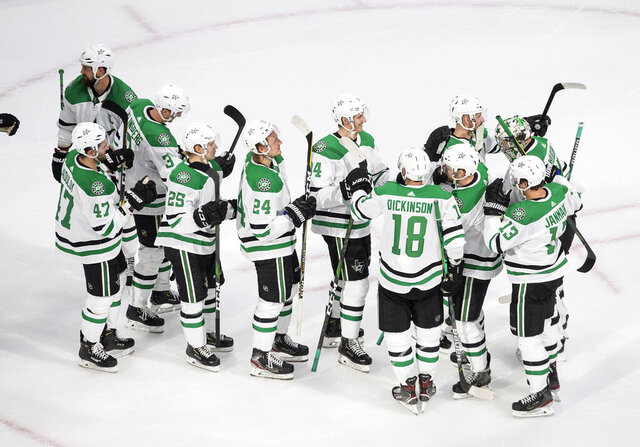 The Dallas Stars celebrate their win over the St. Louis Blues in a shootout during NHL hockey Stanley Cup qualifying round game action in Edmonton, Alberta, Sunday Aug. 9, 2020. (Jason Franson/The Canadian Press via AP)