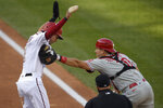 Philadelphia Phillies catcher J.T. Realmuto (10) reaches for Washington Nationals' Trea Turner, left, with his glove as he holds onto the ball in his right hand during the third inning of the first baseball game of a doubleheader, Tuesday, Sept. 22, 2020, in Washington. Turner was eventually out on the play. (AP Photo/Nick Wass)