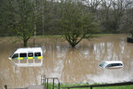 """An ambulance, left, and a vehicle are submerged after flooding in Nantgarw, Wales, Sunday, Feb. 16, 2020. Storm Dennis roared across Britain on Sunday, lashing towns and cities with high winds and dumping so much rain that authorities urged residents to protect themselves from """"life-threatening floods"""