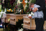 A boy pauses as he speaks next to the coffins of Dawna Ray Langford, 43, and her sons Trevor, 11, and Rogan, 2, who were killed by drug cartel gunmen, during the funeral at a family cemetery in La Mora, Sonora state, Mexico, Thursday, Nov. 7, 2019. Three women and six of their children, all members of the extended LeBaron family, died when they were gunned down in an attack while traveling along Mexico's Chihuahua and Sonora state border on Monday. (AP Photo/Marco Ugarte)