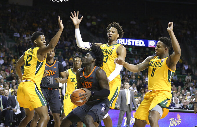Oklahoma State guard Isaac Likekele, center, is guarded by Baylor's Jared Butler, left, Freddie Gillespie and Mark Vital, right, during the first half of an NCAA college basketball game Saturday, Feb. 8, 2020, in Waco, Texas. (AP Photo/Rod Aydelotte)