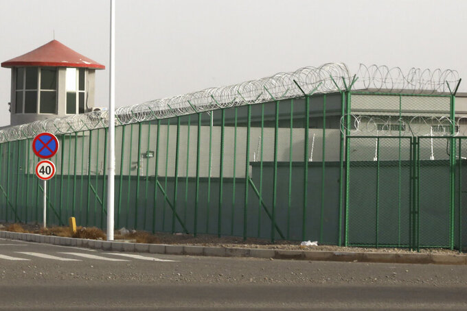 FILE - In this Monday, Dec. 3, 2018, file photo, a guard tower and barbed wire fence surround a detention facility in the Kunshan Industrial Park in Artux in western China's Xinjiang region. A small core of international lawyers and activists are prodding leading Olympic sponsors to acknowledge China's widely reported human-rights abuses against Muslim Uyghurs, Tibetans and other minorities.(AP Photo/Ng Han Guan, File)