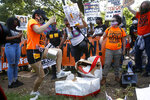 Protesters destroy a mock birthday cake for President Donald Trump on Trump's birthday, Sunday, June 14, 2020, in Lafayette Park near the White House in Washington. (AP Photo/Patrick Semansky)