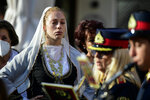 """A woman in traditional dress from the island of Crete attends a procession, ahead of the burial of the late Greek composer Mikis Theodorakis in Chania, Crete island, Greece, Thursday, Sept. 9 2021. Theodorakis died Thursday, Sept. 2, 2021 at 96. He penned a wide range of work, from somber symphonies to popular TV and film scores, including for """"Serpico"""" and """"Zorba the Greek."""" He is also remembered for his opposition to the military junta that ruled Greece from 1967-1974, when he was persecuted and jailed and his music outlawed. (AP Photo/Michael Varaklas)"""