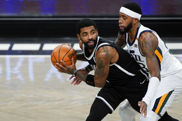 """FILE - Utah Jazz's Royce O'Neale, right, defends Brooklyn Nets' Kyrie Irving (11) during the first half of an NBA basketball game  in New York, in this Tuesday, Jan. 5, 2021, file photo. Kyrie Irving rejoined the Brooklyn Nets on Tuesday, Jan. 19, 2021, saying he took a leave of absence because he """"just needed a pause."""" Irving practiced with the team and could play Wednesday in Cleveland. (AP Photo/Frank Franklin II, File)"""
