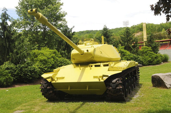 This May 20, 2019 photo shows a M-41 Bulldog World War II period tank that sits at the entrance of Bluefield's Lotito City Park that was mysteriously painted a lemon-lime green color in Bluefield, W.Va.   The Korean War era tank has turned bright lemon-lime yellow thanks to a mix up with paint colors. .(Eric DiNovo/The Daily Telegraph via AP)