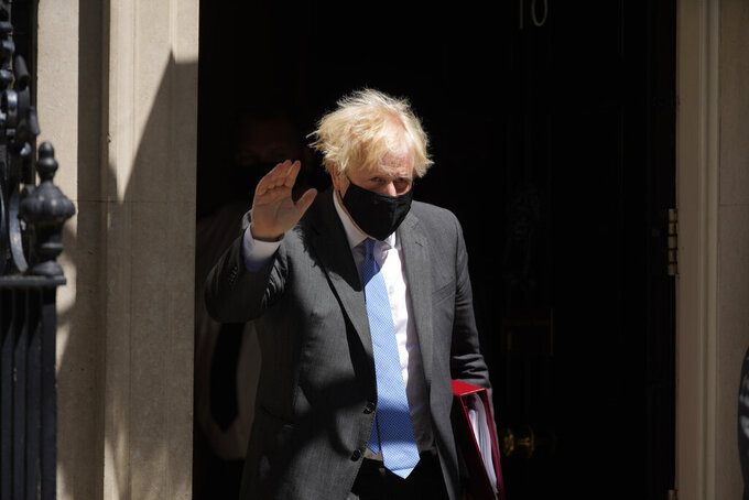 British Prime Minister Boris Johnson waves at the media as he leaves 10 Downing Street to attend the weekly Prime Minister's Questions at the Houses of Parliament, in London, Wednesday, June 16, 2021. (AP Photo/Matt Dunham)