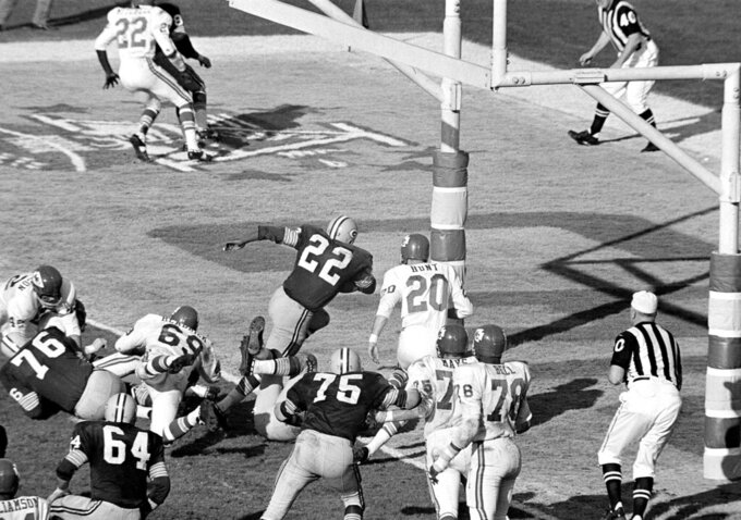 FILE - In this Jan. 15, 1967, file photo, Green Bay Packers' Elijah Pitts (22) charges into the end zone, eluding Kansas City Chiefs' Bobby Hunt (20), during the first Super Bowl in Los Angeles. Pitts scored from the five on the play following Willie Wood's interception in the third quarter. The Packers and the Chiefs had no way of knowing what the Super Bowl would become when they met at Los Angeles Memorial Coliseum on Jan. 15, 1967. (AP Photo/File)