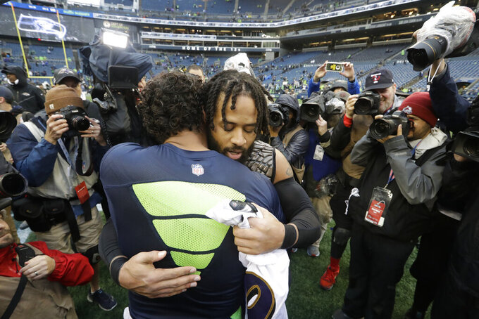 Seattle Seahawks quarterback Russell Wilson, left, hugs Baltimore Ravens free safety Earl Thomas, right, after they traded jerseys following an NFL football game, Sunday, Oct. 20, 2019, in Seattle. (AP Photo/Elaine Thompson)