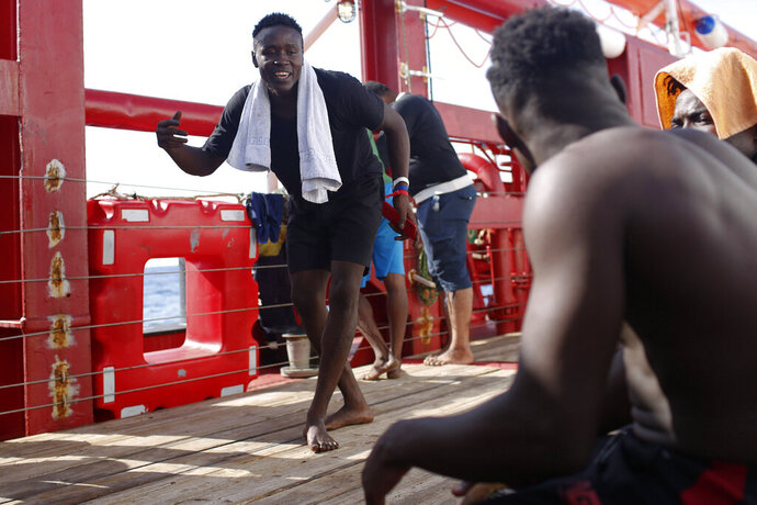 A man dances as another plays the drums aboard the Ocean Viking in the Mediterranean Sea, Thursday, Sept. 12, 2019. Eighty-two rescued migrants remain on board the humanitarian rescue ship waiting for a European country to give them permission to disembark. (AP Photo/Renata Brito)