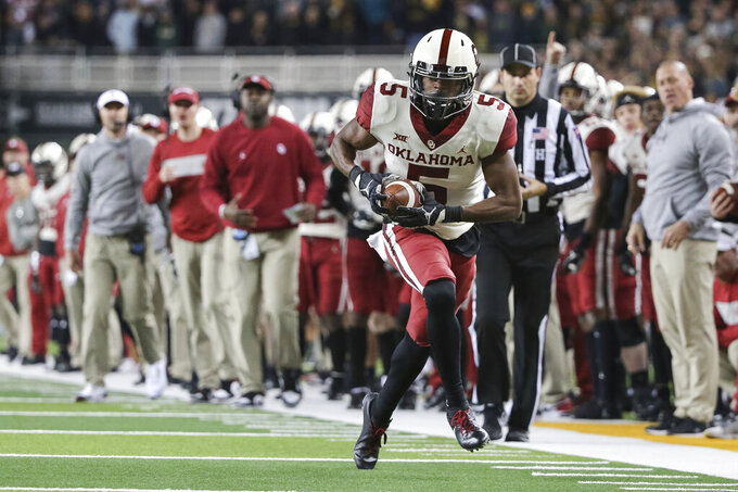 Oklahoma wide receiver A.D. Miller runs after the catch against Baylor during the second half of an NCAA college football game in Waco, Texas, Saturday, Nov. 16, 2019. Oklahoma won 34-31. (AP Photo/Ray Carlin)