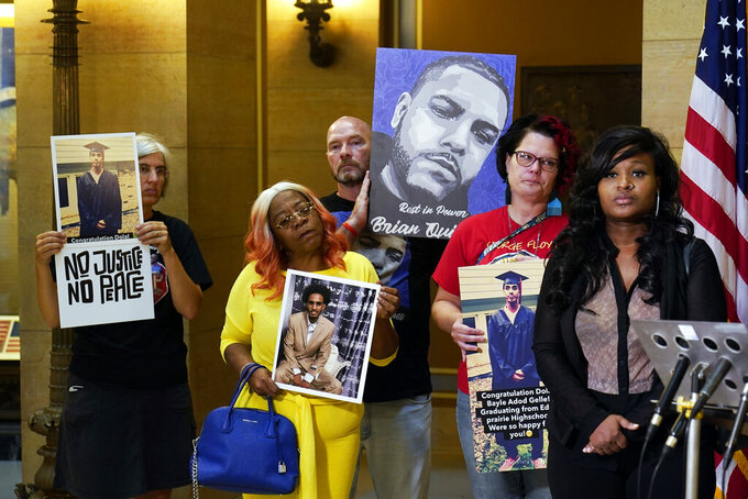 Protesters gathered in the State Capitol rotunda ahead of the debate to urge the Minnesota House to reject the compromise and pass tougher measures in police accountability in the Public Safety Bill, Tuesday, June 29, 2021, in St. Paul, Minn. Listening, right, is Toshira Garraway, founder of Families Supporting Families Against Police Violence, whose fiancé, Justin Teigen, a Black man, was found dead in a recycling bin after fleeing from St. Paul police in 2009, in circumstances that remain in dispute. In red is Courteney Ross, who was George Floyd's girlfriend. (AP Photo/Jim Mone)