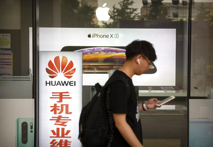A man looks at his smartphone as he walks past an electronics shop advertising phones from Huawei and Apple in Beijing, Friday, May 24, 2019. Stepping up a propaganda offensive against Washington, China's state media on Friday accused the U.S. of seeking to