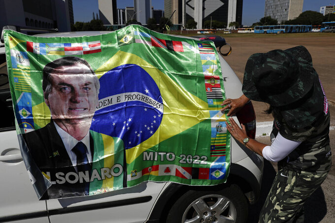 A supporter of Brazilian President Jair Bolsonaro places his image on a car during a gathering commemorating the 1964 military coup that established a decades-long dictatorship, in the Esplanade of Ministries in Brasilia, Brazil, Wednesday, March 31, 2021. The leaders of all three branches of Brazil's armed forces jointly resigned the previous day following Bolsonaro's replacement of the defense minister, causing widespread apprehension of a military shakeup to serve the president's political interests. (AP Photo/Eraldo Peres)