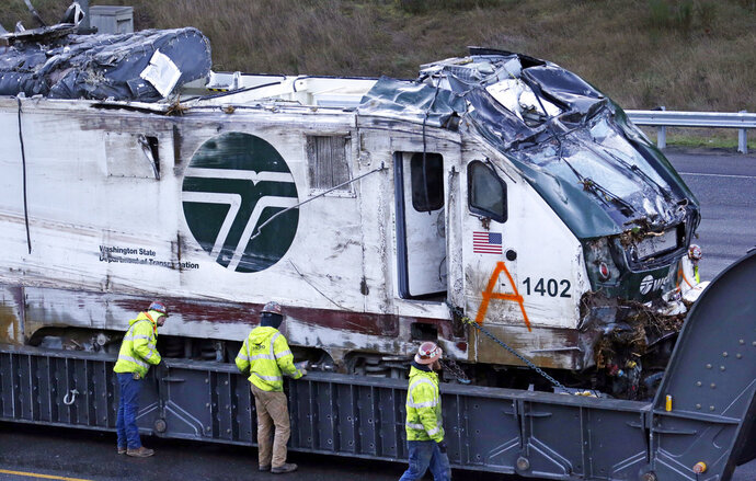 FILE--In this Dec. 20, 2017, file photo, the engine from an Amtrak train that crashed onto Interstate 5 is checked by workers before being transported away from the scene in DuPont, Wash. Federal investigators are hearing from witnesses Tuesday, July 10, 2018 as they look into last year's Amtrak train derailment south of Seattle, Wash., that killed three people and injured dozens. (AP Photo/Elaine Thompson, file)