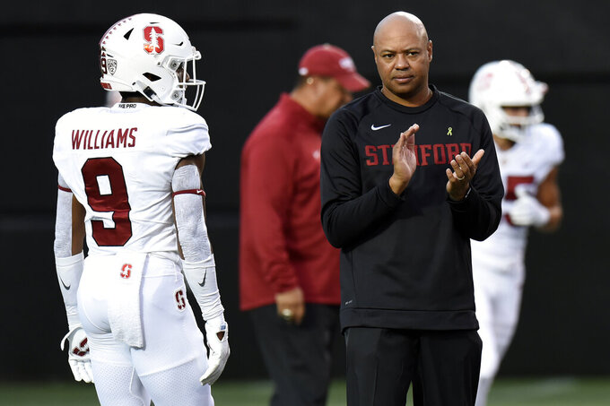 Stanford head coach David Shaw, right, watches players warm up before an NCAA college football game against Vanderbilt, Saturday, Sept. 18, 2021, in Nashville, Tenn. (AP Photo/Mark Zaleski)