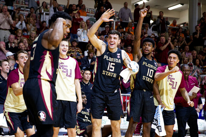 The bench erupts as Florida State guard Trent Forrest (3) flexes after hitting a three-point basket in the second half of an NCAA college basketball game against Tennessee at the Emerald Coast Classic in Niceville, Fla., Friday, Nov. 29, 2019. (AP Photo/Mark Wallheiser)