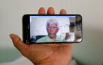 In this Nov. 6, 2019 photo, self exiled Sri Lankan journalist and media rights activist Sunanda Deshapriya is seen on a mobile phone screen during a skype call in Colombo, Sri Lanka.Forced to flee their country a decade ago to escape allegedly state-sponsored killer squads, Sri Lankan journalists living in exile doubt they'll be able to return home soon or see justice served to their tormentors _ whose alleged ringleader could come to power in this weekend's presidential election. Exiled journalists and media rights groups are expressing disappointment over the current government's failure in punishing the culprits responsible for crimes committed against media members. (AP Photo/Eranga Jayawardena)
