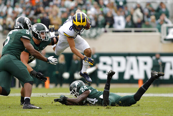 Michigan receiver Ronnie Bell (8) leaps over Michigan State's Tre Person (24) as Michigan State's Andrew Dowell (5) and Kenny Willekes pursue during the second quarter of an NCAA college football game, Saturday, Oct. 20, 2018, in East Lansing, Mich. (AP Photo/Al Goldis)