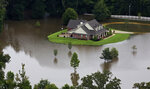 FILE- In this Aug.13, 2016 aerial photo over Amite, La., flooded homes are seen from heavy rains inundating the region. Memories of an epic flood that caused billions of dollars in damage had Louisiana's capital on edge Friday, July 12, 2019, as Barry gained strength in the Gulf of Mexico.(AP Photo/Max Becherer, File)