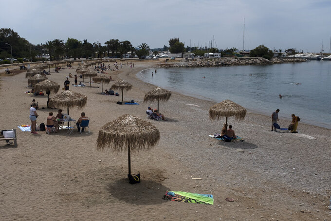 FILE - In this Sunday, May 10, 2020 file photo, people enjoy the beach of Glyfada suburb, southwest of Athens. Greece's Prime Minister Kyriakos Mitsotakis said Wednesday April 21, 2021, the country's tourism industry will open on May 15 when a ban on travel between different regions in the country will be lifted, adding that restaurants and cafes will also be allowed to reopen outdoor areas starting on May 3. (AP Photo/Yorgos Karahalis, File)