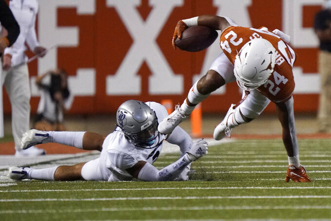 Texas running back Jonathon Brooks (24) is tripped by Rice safety Naeem Smith (3) during the second half of an NCAA college football game on Saturday, Sept. 18, 2021, in Austin, Texas. (AP Photo/Chuck Burton)