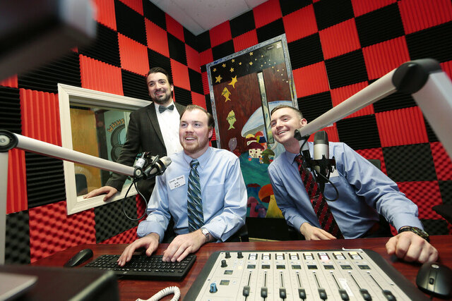 In this Dec. 6, 2019 photo, from left,  Zachary DiFonzo of Drexel Hill, Chris Denny of Ocean City and Jack Walsh of Broomall, get behind the controls in the studio at Haverford High School's WHHS radio station in Havertown, Pa. All graduated in 2009 and were involved with the radio station, Denny was the GM. The radio station was celebrating their 70th anniversary and is the oldest non-commercial educational FM station in the United States. (Elizabeth Robertson/The Philadelphia Inquirer via AP)