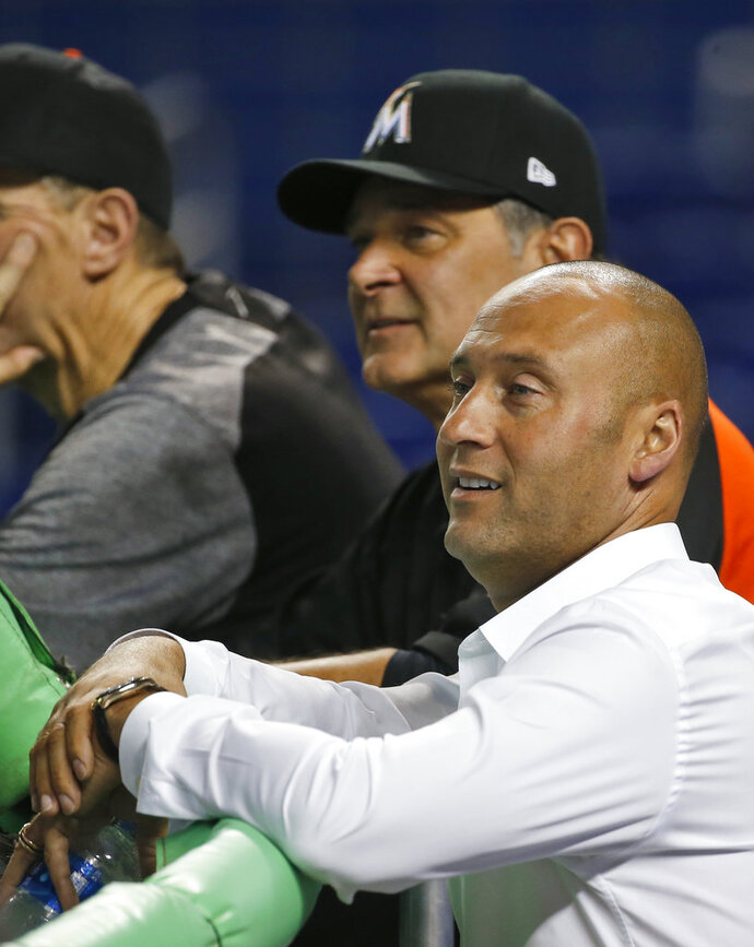 Miami Marlins CEO Derek Jeter, foreground and manager Don Mattingly, rear, watch batting practice before a baseball game against the Los Angeles Dodgers, Wednesday, May 16, 2018, in Miami. (AP Photo/Wilfredo Lee)