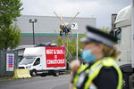 Animal Rebellion protesters suspended from a bamboo structure and on top of a van, being monitored by police officers outside a McDonald's distribution site in Hemel Hempstead, England, Saturday May 22, 2021. Animal rights protesters are blockading four McDonald's distribution centres in the U.K. in an attempt to get the burger chain to commit to becoming fully plant-based by 2025. Animal Rebellion said Saturday that trucks and bamboo structures are being used at the distribution sites in Hemel Hempstead, Basingstoke, Coventry and Heywood, Greater Manchester, to stop lorries from leaving depots.  (Yui Mok/PA via AP)