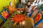 Gloria Arrellano, 68, and her son Gustavo, Arrellano, 36, sit to eat at the Taqueria El Sol buffet in Los Angeles' Boyle Heights neighborhood in Los Angeles, Thursday, July 22, 2021. The restaurant requires all customers to wear face masks while standing in the buffet area of the Mexican restaurant. Gloria Arellano would not let her three sons, or their families visit her in Bakersfield, Calif., until they had been vaccinated. She has personally driven about 10 people to get their vaccine shots. As a cancer survivor and someone who has diabetes, she is not taking any chances that would compromise her health. (AP Photo/Damian Dovarganes)
