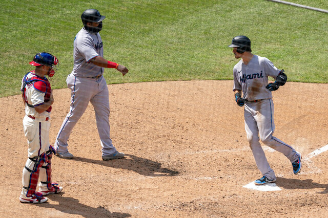 Miami Marlins' Brian Anderson, right, comes in to score on his two-run home run with Jesus Aguilar, center, as Philadelphia Phillies catcher J.T. Realmuto, left, looks on during the fifth inning of a baseball game Sunday, July 26, 2020, in Philadelphia. (AP Photo/Chris Szagola)