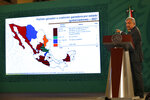 """Mexican President Andres Manuel Lopez Obrador shows the political party makeup of governorships across the country during his daily news conference """"La Mañanera,"""" after weekend mid-term elections at the National Palace in Mexico City, Tuesday, June 8, 2021. (AP Photo/Marco Ugarte)"""