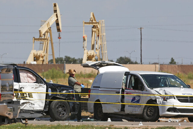 FILE - In this Sunday, Sept. 1, 2019, file photo, law enforcement officials process the crime scene from a shooting the day before which ended with the shooter, Seth Ator, being shot dead by police in a stolen mail van, right, in Odessa, Texas. Federal prosecutors are seeking to keep more than two dozen guns and firearm accessories seized from Marcus Anthony Braziel, whose home was searched in 2019 following a mass shooting in West Texas. The search of Braziel's home last September came days after Ator drove through Odessa and Midland, neighboring cities 140 miles (225 kilometers) south of Lubbock, shooting people before being shot dead by police. (AP Photo/Sue Ogrocki, File)