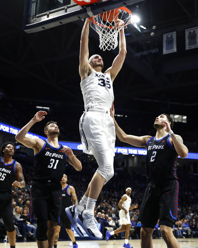 Xavier's Zach Hankins (35) dunks as DePaul's Jaylen Butz (2) looks on during the first half of an NCAA college basketball game, Saturday, Feb. 9, 2019, in Cincinnati. (AP Photo/John Minchillo)