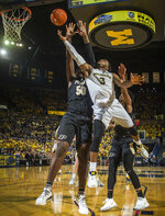 FILE - In this Dec. 1, 2018, file photo, Michigan guard Zavier Simpson (3) goes to the basket defended by Purdue forward Trevion Williams (50) in the second half of an NCAA college basketball game, in Ann Arbor, Mich. Simpson was named to the AP All-Big Ten Conference team, Tuesday, March 12, 2019. (AP Photo/Tony Ding, File)