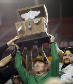 Marshall coach Doc Holliday holds up the trophy after Marshall defeated South Florida 38-10 in the Gasparilla Bowl NCAA college football game Thursday, Dec. 20, 2018, in Tampa, Fla. (AP Photo/Chris O'Meara)