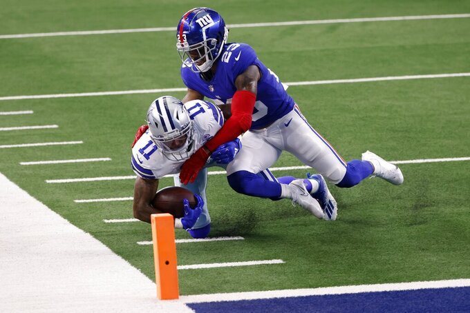 Dallas Cowboys wide receiver Cedrick Wilson (11) catches a pass as New York Giants cornerback Logan Ryan makes the tackle in the first half of an NFL football game in Arlington, Texas, Sunday, Oct. 11, 2020. (AP Photo/Ron Jenkins)