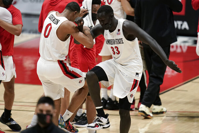 San Diego State forward Keshad Johnson (0) and forward Aguek Arop (33) celebrate after a 62-58 win over Boise State in an NCAA college basketball game Saturday, Feb 27, 2021, in San Diego. (AP Photo/Gregory Bull)