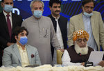 Pakistani opposition parties leaders Maulana Fazal-ur-Rehman, front right, reads out a statement while Bilawal Bhutto Zardari, front left, looks on at a press briefing following their All Parties Conference, in Islamabad, Pakistan, Sunday, Sept. 20. 2020. Pakistani opposition parties demanded immediate resignation of Prime Minister Imran Khan and they launched an alliance to hold a countrywide protest movement against the government. (AP Photo/Anjum Naveed)