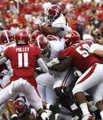 Alabama running back Damien Harris, top, pushes the ball over the goal line to score a touchdown against Arkansas in the second half of an NCAA college football game Saturday, Oct. 6, 2018, in Fayetteville, Ark. (AP Photo/Michael Woods)