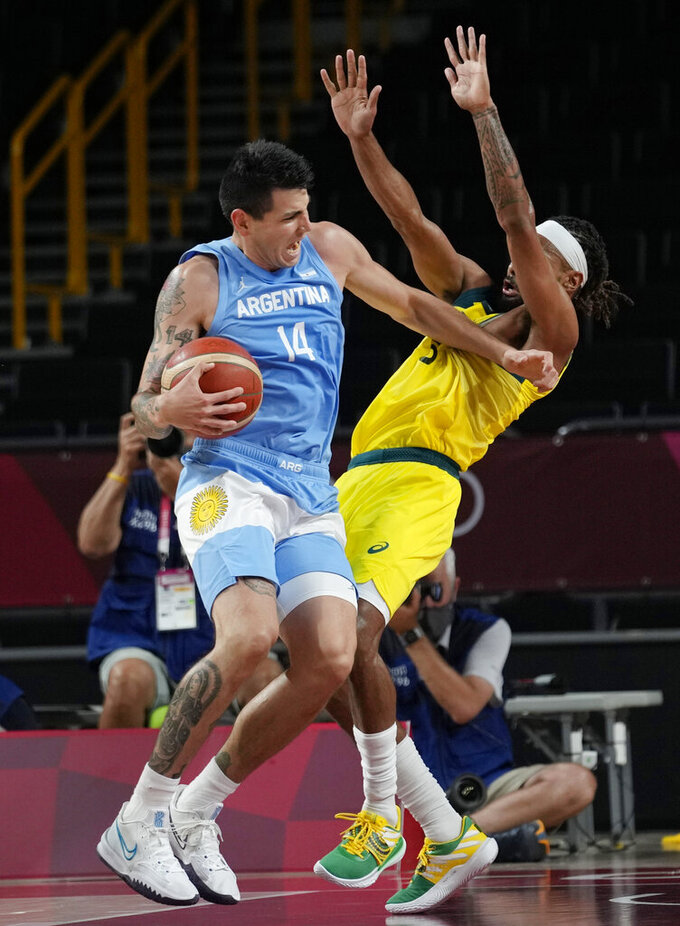 Argentina's Gabriel Deck (14) collides with Australia's Patty Mills (5) as he drives to the basket during a men's basketball quarterfinal round game at the 2020 Summer Olympics, Tuesday, Aug. 3, 2021, in Saitama, Japan. (AP Photo/Eric Gay)