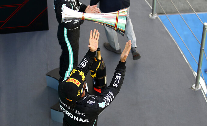 Mercedes driver Lewis Hamilton of Britain celebrates on the podium after winning the Formula One Grand Prix at the Barcelona Catalunya racetrack in Montmelo, Spain, Sunday, Aug. 16, 2020. (Bryn Lennon, Pool via AP)