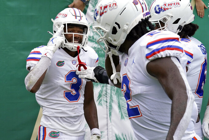 Florida wide receiver Xzavier Henderson (3) celebrates with teammates after his touchdown reception against South Florida during the first half of an NCAA college football game Saturday, Sept. 11, 2021, in Tampa, Fla. (AP Photo/Chris O'Meara)