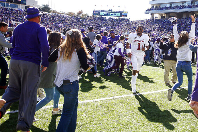 Kansas State fans storm the field as Oklahoma quarterback Jalen Hurts (1) attempts to head towards the locker room after the Sooners loss to the Wildcats in an NCAA football game at Bill Snyder Family Stadium in Manhattan, Kan., Saturday, Oct. 26, 2019. (Ian Maule/Tulsa World via AP)