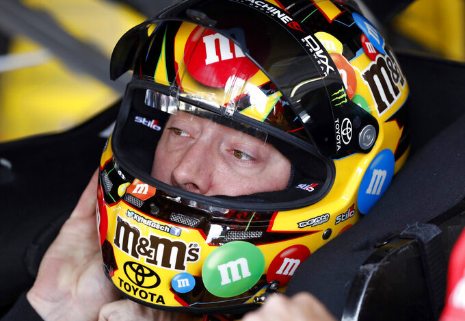 Driver Kyle Busch dons his helmet before practicing for the NASCAR Cup Series auto race at Kansas Speedway in Kansas City, Kan., Friday, May 10, 2019. Busch leads the series in points. (AP Photo/Colin E. Braley)